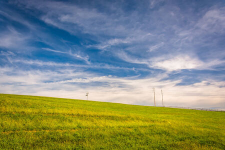 over hill: Wispy clouds over a grassy hill in York County, Pennsylvania.