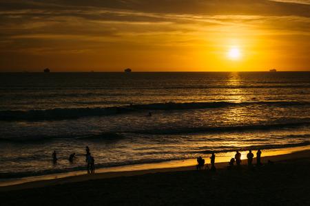 huntington beach: People on the beach and sunset over the Pacific Ocean in Huntington Beach, California.
