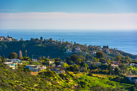 overlooking: View of green hills and houses overlooking the Pacific Ocean, in Laguna Beach, California.