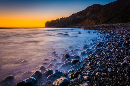 Long exposure of waves crashing on rocks at sunset, taken at Pelican Cove, in Ranchos Palos Verdes, California.