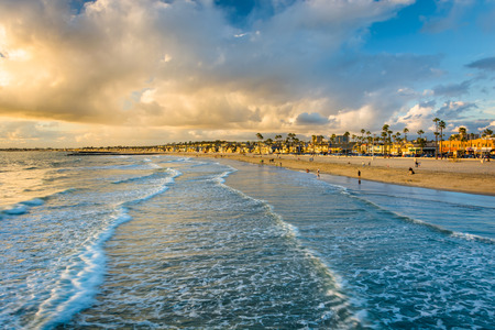 Golven in de Stille Oceaan en uitzicht op het strand bij zonsondergang, in Newport Beach, Californië