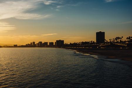 long: Buildings along the shore at sunset in Long Beach, California.