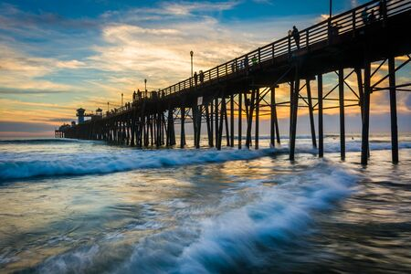 oceanside: The pier and waves in the Pacific Ocean at sunset, in Oceanside, California.