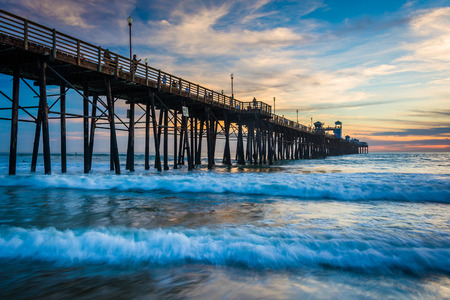 The pier and waves in the Pacific Ocean at sunset, in Oceanside, California.