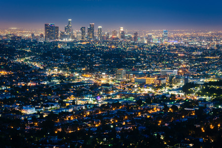 overlooking: View of the downtown Los Angeles skyline at night, from Griffith Observatory, in Griffith Park, Los Angeles, California. Stock Photo