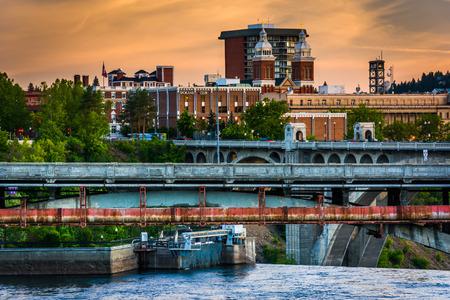Bruggen over de rivier de Spokane en gebouwen bij zonsondergang, in Spokane, Washington. Stockfoto