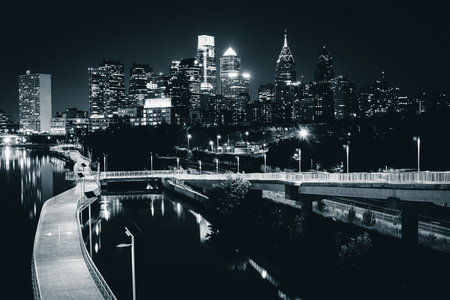 dark city: The skyline and Schuylkill Banks Boardwalk seen at night from the South Street Bridge over the Schuylkill River, in Philadelphia, Pennsylvania.