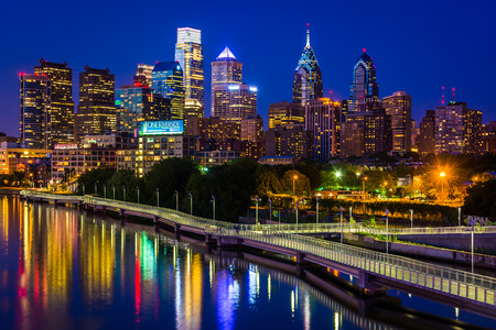 lights on: The Philadelphia skyline and Schuylkill River at night, seen from the South Street Bridge in Philadelphia, Pennsylvania.