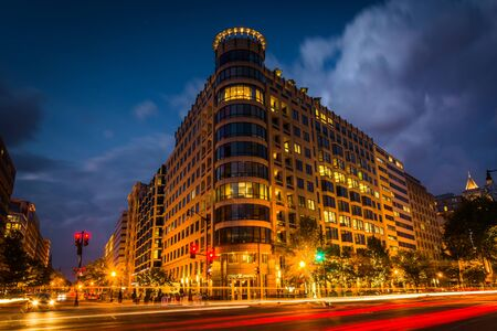 Long exposure of traffic on K Street and a modern building at night, in Washington, DC.