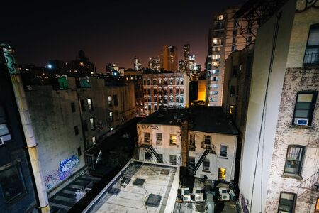 View of buildings in the Lower East Side from the Manhattan Bridge Walkway at night, in Manhattan, New York.