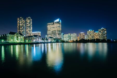 shore: Buildings along the waterfront at night, in Jersey City, New Jersey. Stock Photo