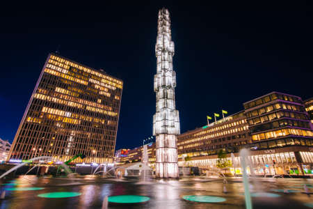 Glass obelisk and fountains in the traffic circle at night, at Sergels torg, in Norrmalm, Stockholm, Sweden.