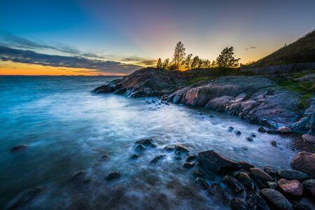 Sunset over rocky coast on Suomenlinna, in Helsinki, Finland.
