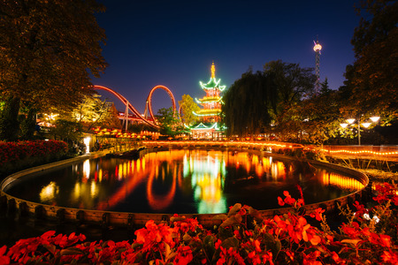 danmark: The Japanese Tower and rides at night, reflecting in a lake at Tivoli Gardens, in Copenhagen, Denmark.