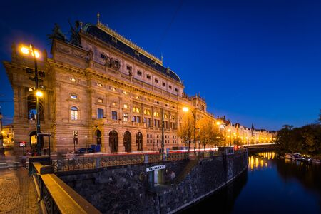 The Legion Bridge and buildings along the Vltava at twilight, in Prague, Czech Republic.