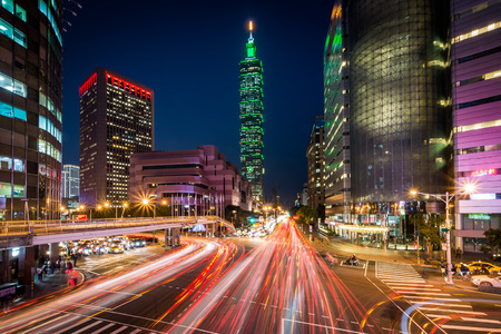 Traffic on Xinyi Road and view of Taipei 101 at night, in Taipei, Taiwan. Фото со стока