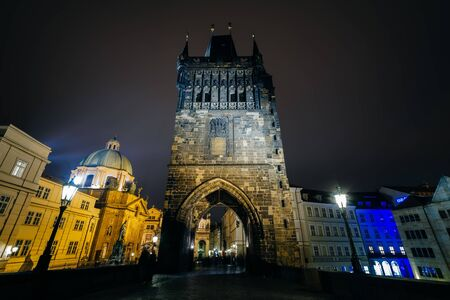 A tower of the Charles Bridge at night, in Prague, Czech Republic.