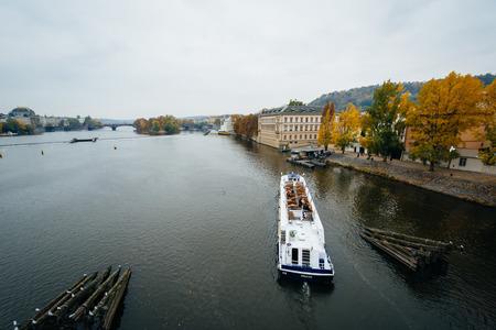 Boat in the Vltava, on a cloudy autumn day, in Prague, Czech Republic.