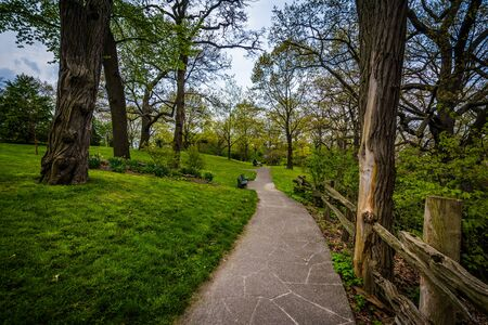 high park: Fence and trees along a walkway at High Park, in Toronto, Ontario. Stock Photo