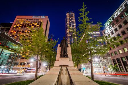 median: Statue of Adam Beck in the median of University Avenue, and modern buildings in downtown Toronto, Ontario.