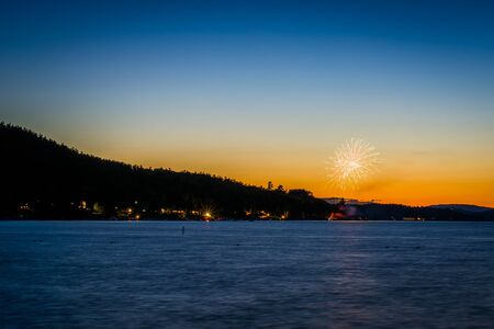 laconia: Fireworks and Lake Winnipesaukee at sunset, at Ellacoya State Park, in Laconia, New Hampshire.