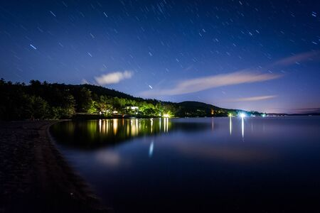 long lake: Long exposure of stars moving over Lake Winnipesaukee at night, at Ellacoya State Park, in Laconia, New Hampshire.