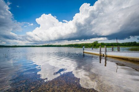 auburn: Dramatic storm clouds over a dock in Massabesic Lake, in Auburn, New Hampshire. Stock Photo