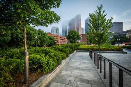north end: Walkway and gardens at North End Park with view of buildings in downtown in fog, in the North End, Boston, Massachusetts. Stock Photo