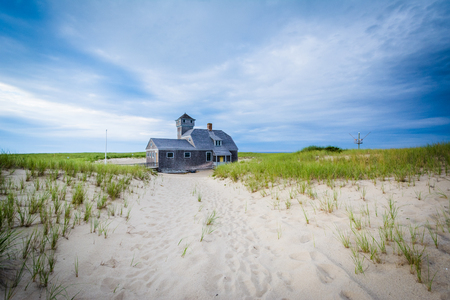 Sand dunes and grasses, and the Old Harbor U.S. Life Saving Station, at Race Point, in the Province Lands at Cape Cod National Seashore, Massachusetts. Stock Photo