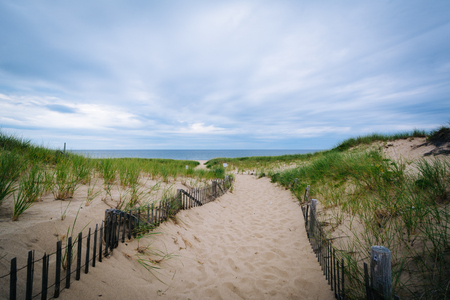 Fence and path through sand dunes at Race Point, in the Province Lands at Cape Cod National Seashore, Massachusetts. Stock Photo