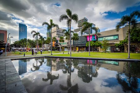 Palm trees and modern buildings reflecting in a pool at Bonifacio Global City, in Taguig, Metro Manila, The Philippines.