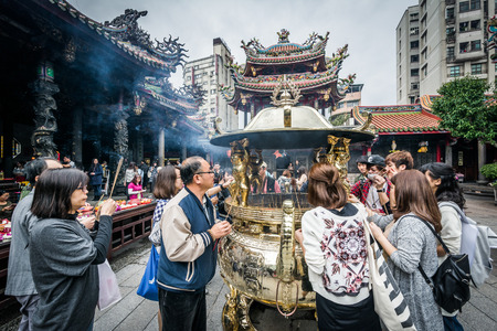 The burning of incense sticks, at Longshan Temple in the Wanhua District of Taipei, Taiwan.
