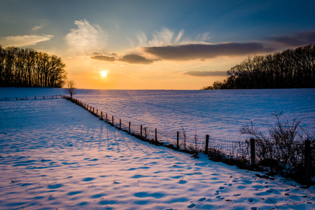 Winter sunset over a fence and snow covered farm field in rural Carroll County, Maryland.