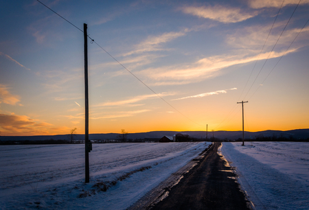 covered fields: Sunset over a country road through snow covered fields in rural Frederick County, Maryland.