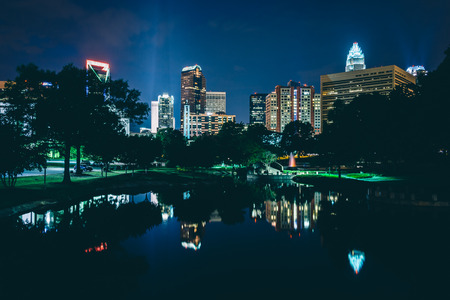 charlotte: The Uptown skyline and a lake at Marshall Park at night, in Charlotte, North Carolina.