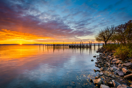 Sunrise over dock and the Chesapeake Bay, in Havre de Grace, Maryland. Фото со стока