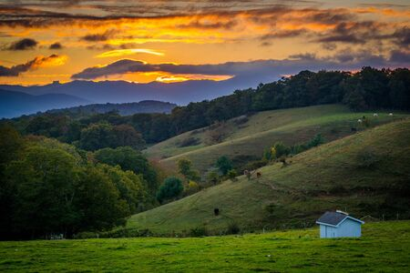 Sunset over rolling hills and farm fields at Moses Cone Park on the Blue Ridge Parkway in North Carolina.