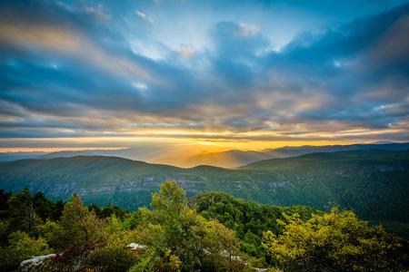 リンビル渓谷ノースカロライナ州ピスガ国有林の縁にテーブル ロックからブルーリッジ山脈に沈む夕日。