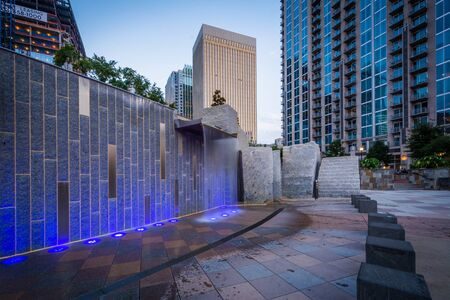 Fountain and modern buildings at twilight, seen at Romare Bearden Park, in Uptown Charlotte, North Carolina. Stock Photo