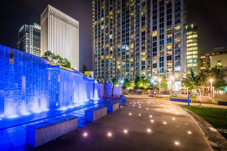 Fountain and modern buildings at night, seen at Romare Bearden Park, in Uptown Charlotte, North Carolina.