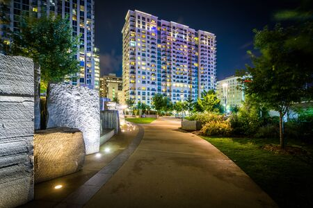 Walkway and modern buildings at night, seen at Romare Bearden Park, in Uptown Charlotte, North Carolina.