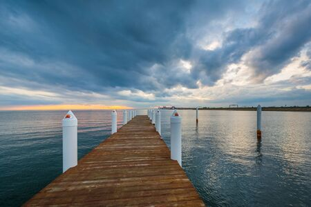 Dramatic sunset over a pier in the Chesapeake Bay, in Kent Island, Maryland.