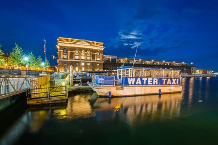 A water taxi along the Fells Point Waterfront at night, in Baltimore, Maryland. Editorial
