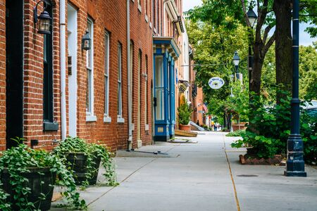 Brick rowhouses and sidewalk on Bond Street in Fells Point, Baltimore, Maryland. Editorial