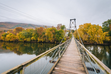 Swinging bridge over the James River and fall color in Buchanan, Virginia