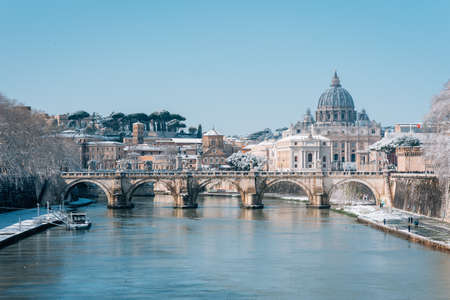Ponte Sant'Angelo and St. Peter's Basilica in the snow, in Rome, Italy.