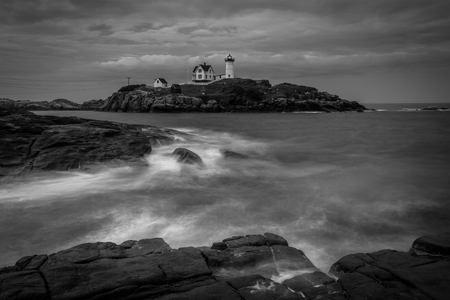 Long exposure of waves crashing on rocks in the Atlantic Ocean, and the Nubble Lighthouse, at Cape Neddick, in York, Maine. Stock Photo