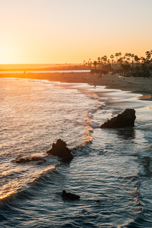 Waves and rocks in the Pacific Oean at sunset, in Corona del Mar, Newport Beach, California