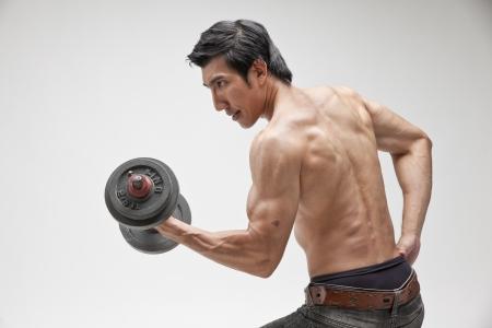 muscle shirt: hombre musculoso posando con la mancuerna