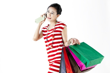 Woman in red stripes dress on phone while carrying shopping bags isolated on white photo